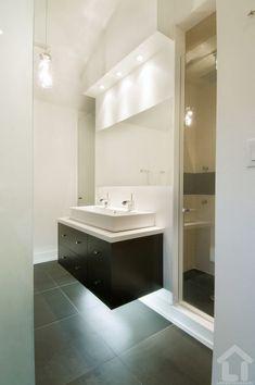 Tiszta, világos fürdőszoba kompozíció, melyet változatos világítás tesz érdekessé
