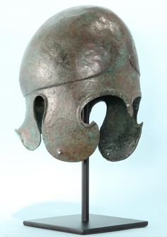 Greek bronze Chalcidian helmet. An applique in the form of a Gorgoneion (a Medusa head) is attached to the top of the helmet. Ca. 520-480 BC. H. 24 cm. Chalcidian helmet began to replace the more restrictive Corinthian helmet on Greek battlefield in 5th c BC. The Chalcidian is characterized by its carinated design and diminutive cheek pieces that left face exposed and provided openings for ears. This helmet type was especially popular in Southern Italy in the Classical and Hellenistic…