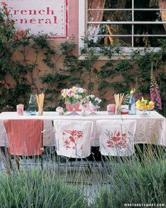 French Courtyard Table - Set a thoroughly charming table inspired by French linens and flowers. Flower sack fabric covers folding chairs; small bouquets of roses dot the table. French lemons and bottles of water are the only other adornment.