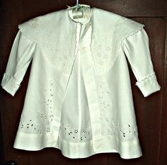 Here's a lovely children's white pique coat from the late Victorian - Edwardian era. The spring or summer coat is made of very fine pique fabric, styled with a large shawl collar. Beautiful cutwork
