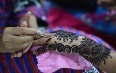 A Pakistani beautician applies traditional henna design to the hand of a customer in Karachi on August 7, 2013. AFP Photo / Asif Hassan