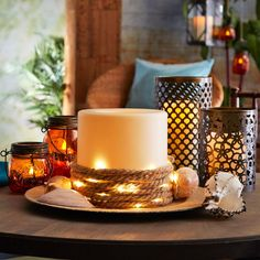 Add light and interest to a large candle with a Lighted Rope and sea shells to create this nautical inspired decor piece