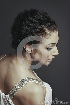 Side face portrait of beautiful female fashion model posing with braided hairdo, wearing white low cut blouse, looking down over grey background.