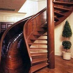 Spiral staircase, fun house, sliding down the banister, wooden slide, taking the quicker way.