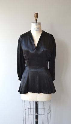 Vintage 1930s black silk satin blouse with V neckline, 3/4 sleeves, fitted waist, peplum and side metal zipper. --- M E A S U R E M E N T S ---  fits like: large bust: 40-42 waist: 32 length: 28 brand/maker: n/a condition: excellent  To ensure a good fit, please read the sizing guide: http://www.etsy.com/shop/DearGolden/policy  ✩ more vintage dresses ✩ http://www.etsy.com/shop/DearGolden?section_id=5986725  ✩ visit the shop ✩ http://www.DearGolden.etsy.com  _____________________  ➸ instagram…