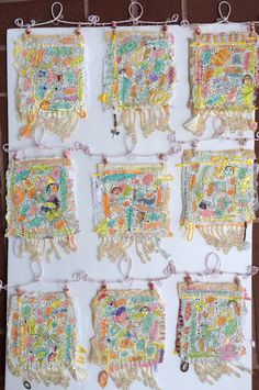 Series of nine handmade paper pieces with wire hangers and fringe.