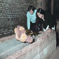 """Olivia Hussey and Leonard Whiting, who played the title roles in Franco Zeffirelli's """"Romeo and Juliet,"""" place flowers on the """"Tomba di Giulietta"""" in Verona, Italy, on Oct. 22, 1968. (AP Photo)"""