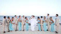 Bridesmaids in long light blue dresses and groomsmen in khaki suits. Wedding party portrait on the beach. | Palace Resorts Weddings ®