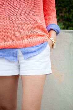 white shorts, chambray shirt, and coral sweater