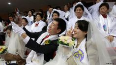 February 12, 2014. A couple take a selfie before a mass wedding ceremony at the CheongShim Peace World Center in Gapyeong, South Korea. Around 2,500 South Korean and foreign couples exchanged or reaffirmed marriage vows in the Unification Church's mass wedding.
