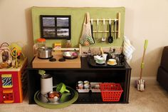 inexpensive diy play kitchen using cardboard box as background. hot glue picture frame as window, coasters as back splash, painted baby food jar lids as stove knobs that make popping sounds. #toddler #play #provocation