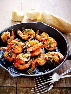 Scampi in Öl und Knoblauch braten, dazu Baguette und Wein.