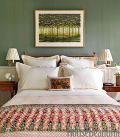 In an East Hampton bedroom, an April Gornik painting is set off by walls in Tavern Green by The Old-Fashioned Milk Paint Co.. Designer Bunny Williams chose an Indonesian quilt for its texture