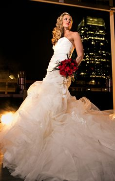 Bride poses with red bouquet, photographed by Candice Jones Photography. Featured in the Summer 2013 issue of the Nashville Pink Bride Magazine - The Pink Bride www.thepinkbride.com {Fashion Shoot: Vintage Glamour at the Nashville Hard Rock Cafe}
