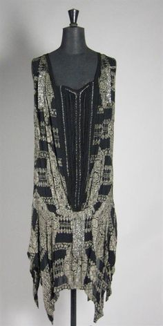 A fine brocaded metallic silver-grey and black flapper dress with faggot stitching to the front panel and a fringe of silver beads. The faggoting interspaced with clear beads. The hemline with handkerchief points. 1920s. Probably French
