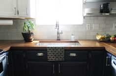 Chris Loves Julia: The Kitchen: Before and Afters! navy lower cabinets with white uppers. took down some uppers and replaced with open shelves. dark door with windows. cute!!