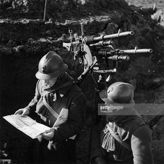 French soldiers read a newspaper in the trenches during World War II.