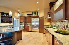Large modern wood kitchen design with large round and square island creating a large eat-in area.