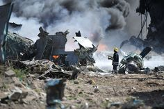 FIGHTING FLAMES: A firefighter attempted to extinguish a fire at the site of an airplane crash in Mogadishu, Somalia, Friday. An Ethiopian military aircraft crashed upon landing at Mogadishu airport, killing four crew members. (Tobin Jones/Associated Press)