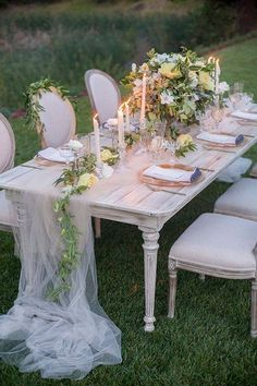 A table runner of sheer fabric flows softly to the ground at a garden wedding ~