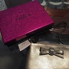 Authentic Coach very small gunmetal handbag This is so cute, Brand New with Tags!!!!! Comes with coach gift box. Length is 6 inches width and 4 inches long. Has a handle. Zips up has a small compartment for cards. Can fit a small cell phone. Metallic gunmetal. Coach Bags Clutches & Wristlets