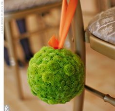 The Ceremony Decor: Small pomanders of green button mums to attach to the gold chiavari chairs and tied them off with orange ribbon.