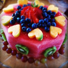 Fruit Birthday cake, the main part is watermelon. The garnishing are kiwis, blueberries, strawberries, melon and grapes. All natural. No sugar, no flour, no icing, no eggs .. just fruit.  Yum!