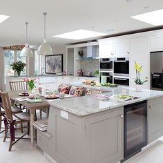 Flat roof windows were included in the roof boosting brightness in this contemporary kitchen. In addition to spotlights, pendant shades in a muted tone match the painted furniture, creating a smart feature that makes a focal point of the seating. Read more at www.housetohome.co.uk/kitchen/picture/pale-grey-kitchen-with-island-unit#VKSJgCuS8DZoZvJW.99 Housetohome.co.uk