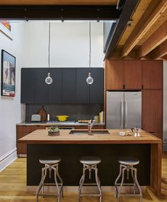 A modern kitchen with high ceilings, warm wood countertops, black cabinets, center island, hanging exposed lightbulbs, tile backsplash, stainless steel appliances and studio stools.