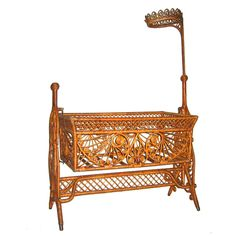 "Natural finish Victorian wicker cradle with an artistically inspired sculptural quality. A melange of symmetrical reed curlicues and diagonal latticing fill the body of the cradle. Removable wicker ""crown"" fits into the taller intricately twisted ball finial. Mosquito netting would be gathered at the crown and draped over the cradle as a canopy to protect the baby from insect bites. The swinging cradle is held by a separate 4-legged bentwood frame"