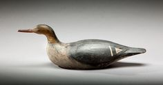 Swimming Merganser Hen Luther M. Nickerson (1874-1951) Cotuit, MA, c. 1920 A fine example of a working Cape Cod sea duck decoy. The bird displays glass eyes, carved bill detail, and the maker's classic raised wings. Original paint with gunning wear and craquelure. Touch-up to a neck crack.
