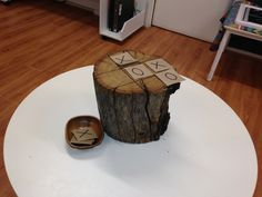 Bringing outside inside. Using tree stumps for little cognitive games such as naughts and crosses is an easy way to bring nature into experiences yet effective.