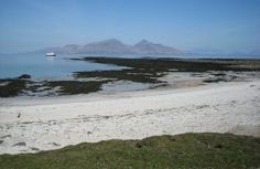 Remote beach on the Island of Muck and in the distance you can see the Island of Rum, Inner Hebrides, Scotland.