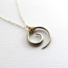 The koru is a Maori symbol of strength, peace and new life. This designer's jewelry is so awesome. Kahili Creations