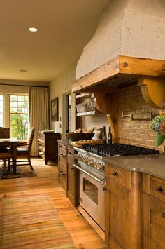 Love the modern stove with the wooden cabinets.