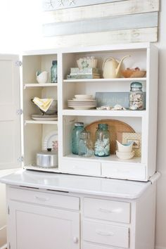 Gorgeous beach house decor.  White, cream, beige kitchen, with blue ball jars for storage.