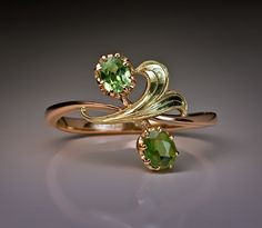 A 14K rose and greenish-yellow gold ring, circa 1910, designed as an Art Nouveau flower, featuring two Russian Uralian demantoids.