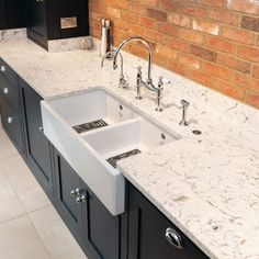 A double butler sink from Shaw's and a Perrin & Rowe tap are included in the kitchen design. The taps include an instant boiling water tap and a pull-out rinse. The Quartz Worktop is by Urban Quartz and is called Bianco Foresta. Modern Shaker Kitchen, Shaker Style Kitchens, Kitchen With Long Island, Long Kitchen, Exposed Brick Kitchen, Bar Dining Table, Butler Sink, Shaker Furniture, Built In Ovens