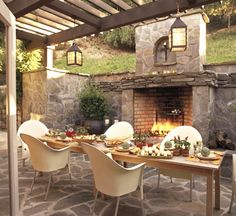 Fireside Table:Rustic walls, floors, and a large fireplace envelop this open-air room, lending a sense of intimacy to the space. Contemporary chairs and a sleek dining table in teak bring stylistic balance to the room's rough-hewn, camp-like character.