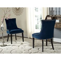 Low sloped arms and a slight hourglass shape to the seat back define this set of two dining chairs upholstered in cotton velvet in navy blue.