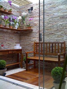 Pequeno jardim com orquídeas e paredes revestidas com canjiquinha.  Fotografia: www.decorfacil.com