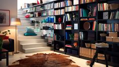 A living room wall and stairway full of black bookshelves