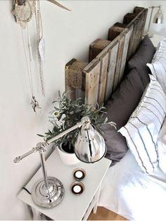 Dans une chambre d'adulte, la tête de lit fabriquée avec deux palettes de bois brute pour complèter l'ambiance couleurs naturelles de la cha...