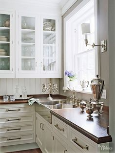 Sunlight filters in to this butler's pantry illuminating polished nickel and silver finishes along with gleaming white cabinetry. Simply styled cabinets and a tongue-and-groove-paneled backsplash puts the attention on drawer hardware and the silver sink.