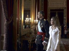 Facing a nation: King Felipe VI appeared humbled by his country as he clasped his wife's hand and stepped onto the palace balcony to wave to his people.