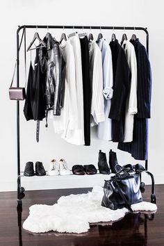 Keep your closet simple with a black clothing rack—it's easy for organization and acts as decor against a blank wall. - HarpersBAZAAR.com