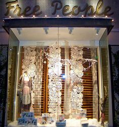 Display on a budget: use paper or cloth doilies to create a dramatic winter display.  We're loving this Free People window display.