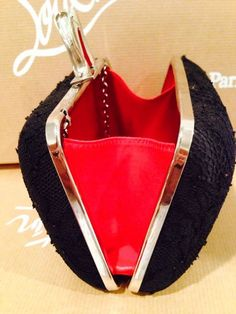 CHRISTIAN LOUBOUTIN CLUTCH -  With a red lining, this Christian Louboutin clutch is ready for a romantic night out.