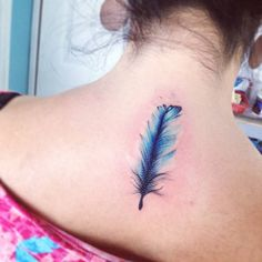 Blue watercolor style feather tattoo on the upper back. Tattoo...