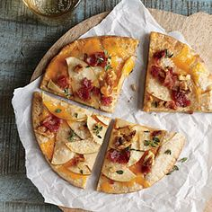 Apple and bacon pita pizzas. Smoky bacon, rich walnuts, and woodsy thyme give depth to these quick personal pizzas.